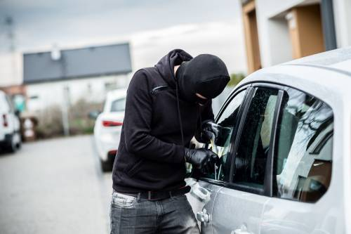 Man wearing balaclava attempting to break into a car