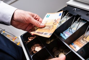Man taking European currency out of a cash register