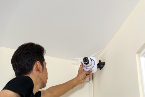 Man installing a residential security camera
